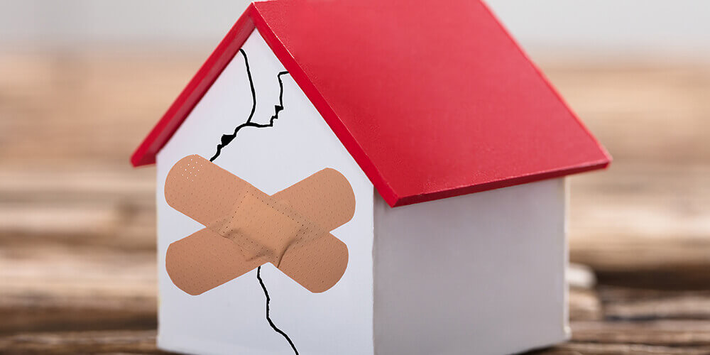 Broken house represent that little debt can be leverage, but if too much, it crushes.